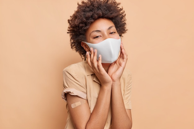 Portrait of curly haired young woman keeps hands on face wears protective mask adhesive plaster on arm being vaccinated against coronavirus isolated over beige wall