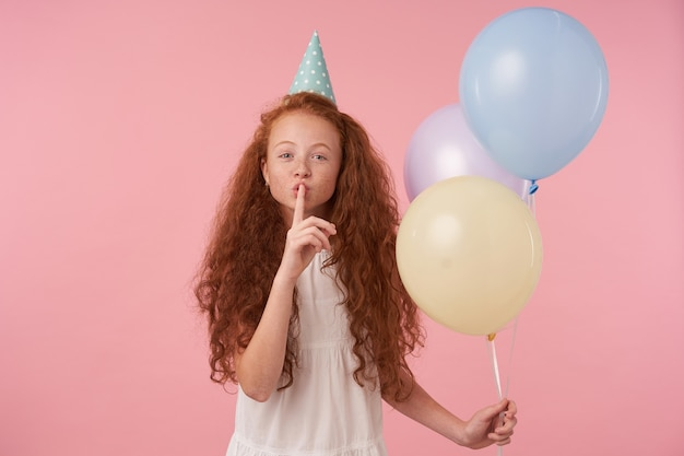 Portrait of curly long haired little girl in festive clothes and birthday cap posing over pink background, keeping forefinger on her lips and asking to keep secret. children and celebration concept