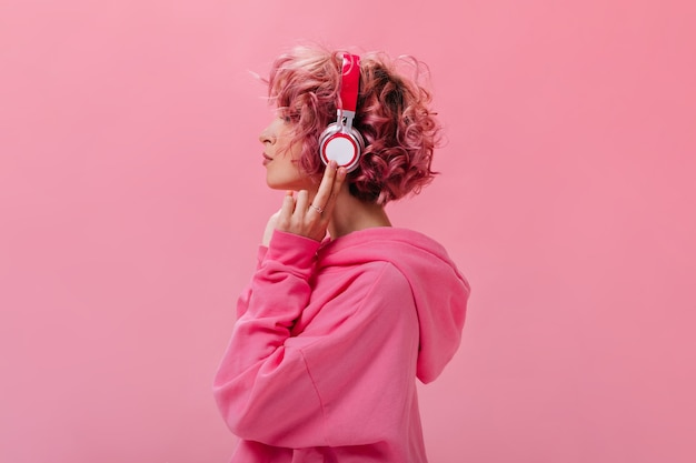 Portrait of curly pink haired woman in massive white headphones