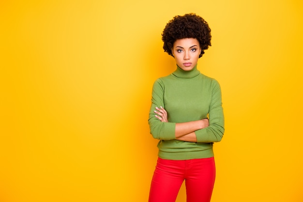 Portrait of curly wavy serious confident woman with hands folded in red pants looking at you with clever eyes.