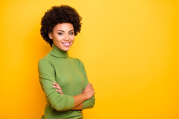 Portrait of curly wavy trendy cheerful positive turned woman with arms crossed looking at you with toothy smile.