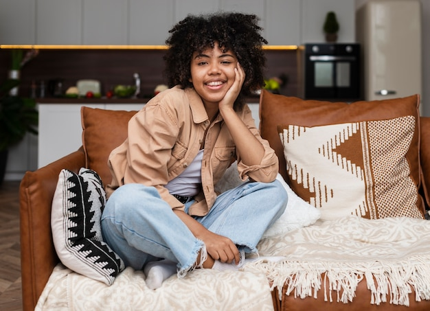 Portrait of curly woman sitting on sofa