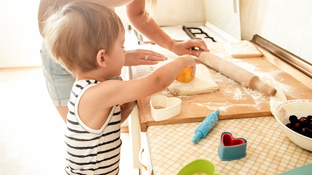 Portrait of cute 3 years old toddler boy cooking cookies with mother