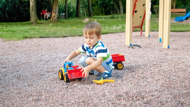 Portrait of cute 3 years old toddler boy sitting on the playground at park and playing with colorful plastic toy truck