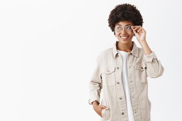 Ritratto di carino adorabile donna adulta afro-americana in camicia beige e occhiali toccando il bordo degli occhiali mentre sorride con gioia e guardando a sinistra controllando i negozi che passano camminando lungo la città