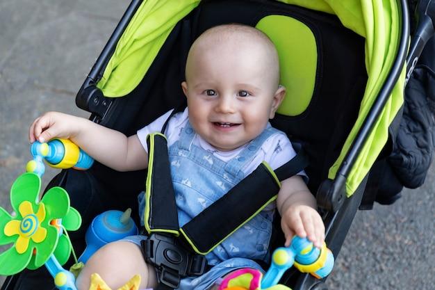 A portrait of cute adorable baby boy is sitting in modern stroller wearing seat belts on a walk in the street.
