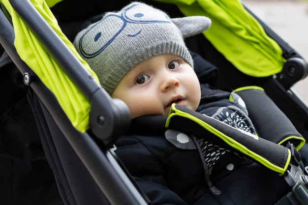 A portrait of cute adorable baby boy is sitting in the stroller