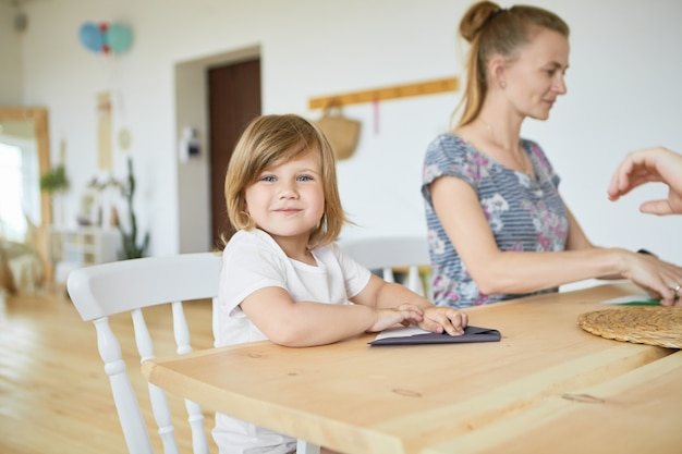 Portrait of cute adorable baby girl in white t-shirt sitting at wooden dining table wiht her mother, learning how to make origami paper plane,  with happy smile. selective focus