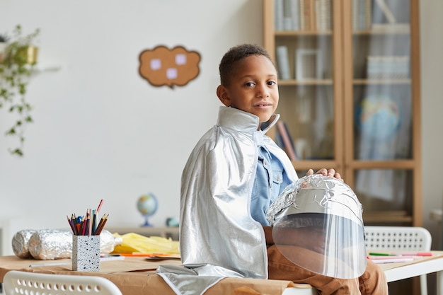 Portrait of cute african-american boy playing astronaut while enjoying art and craft lesson in preschool or development center