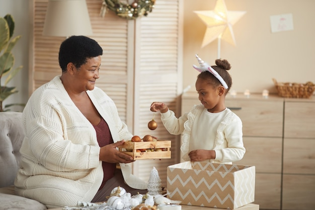 Portrait of cute african-american girl opening box of christmas decorations while preparing for christmas celebration with loving grandma, copy space