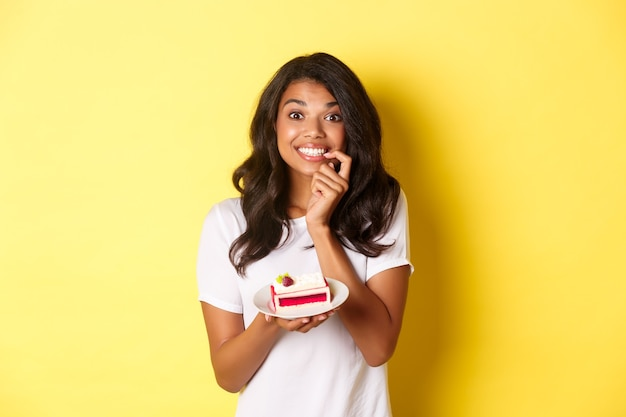 Portrait of cute african-american girl smiling, holding delicious piece of cake, temted to eat dessert, standing over yellow background