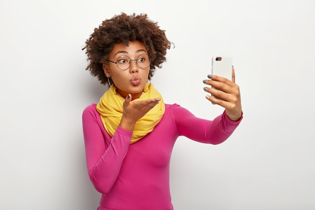 Portrait of cute african american woman sends air kiss, takes selfie via smartphone, wears transparent glasses, makes rounded lips, wears vivid clothes, isolated over white wall.