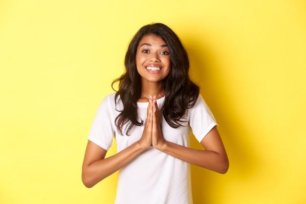 Ritratto di donna afroamericana carina, sorridente e tenendosi per mano in preghiera, dicendo grazie, sentendosi grata, in piedi su sfondo giallo.