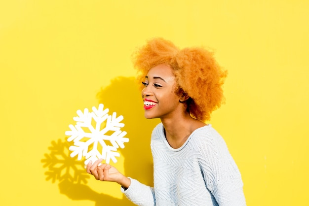 Portrait of a cute african woman in blue sweater holding an artificial snowflake on the yellow background