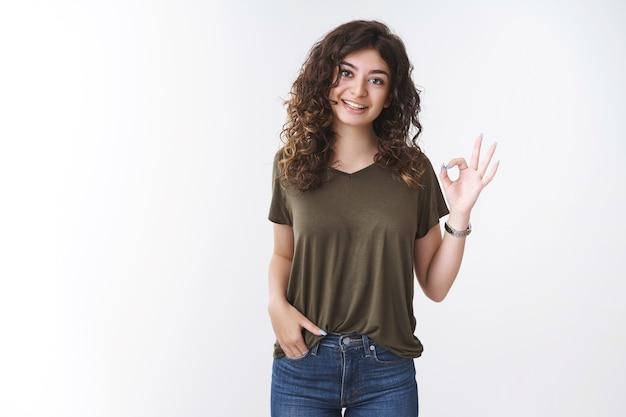 オリーブのtシャツを着た肖像画のかわいいアルメニアの縮れ毛の女性は大丈夫ジェスチャーを示しています服装は悪くないことを考えて同意します