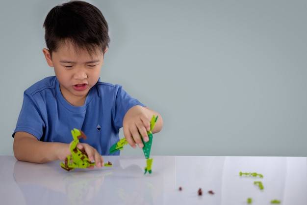 Portrait of cute asian boy playing with colorful plastic toy bricks