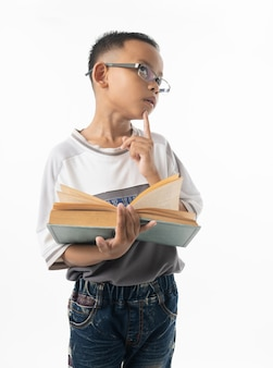 Portrait of cute asian boy student thinking and holding big book