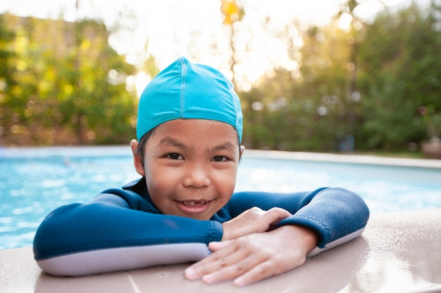 Portrait of cute asian child girl wearing swimming suit in the swimming pool