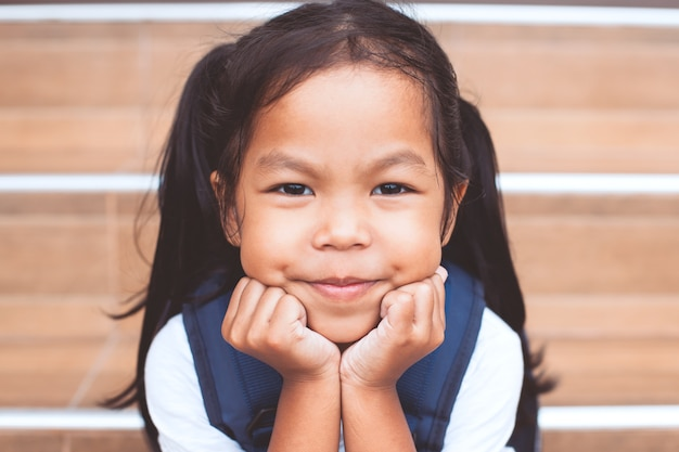 Portrait of cute asian child girl with school bag smiling at school