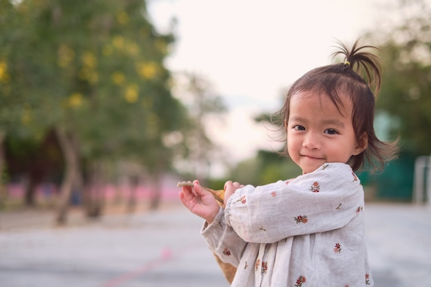 Portrait of cute asian happy little toddler baby child girl looking at and camera and smiling in a park in spring time