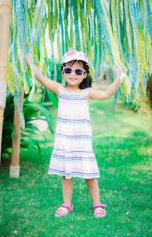 Portrait of cute asian little girl wear sunglasses and hat in the park