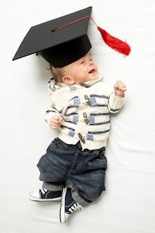 Portrait of cute baby boy lying in graduation hat on bed
