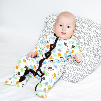 Portrait of a cute baby lying down on a bed, top view.