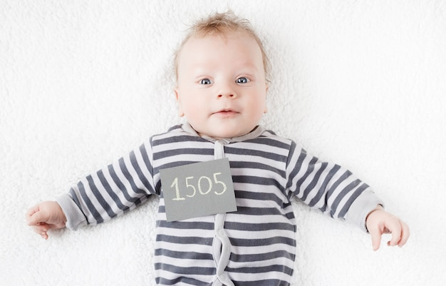 Portrait of a cute baby in a striped suit with a sign on his chest