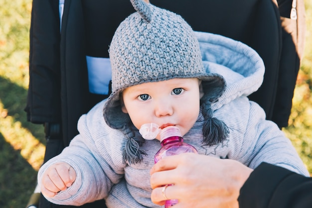 Portrait of a cute baby on a walk outdoors. child sits in a stroller and drinking water from bottle.
