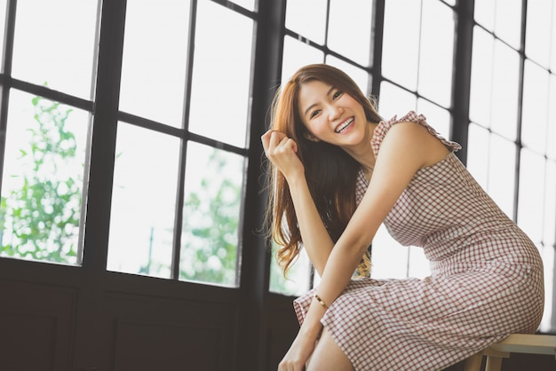 Portrait of cute and beautiful asian girl smiling in coffee shop or modern office with copy space