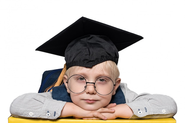 Portrait of a cute blond boy in big glasses, academic hat and a backpack. isolate.
