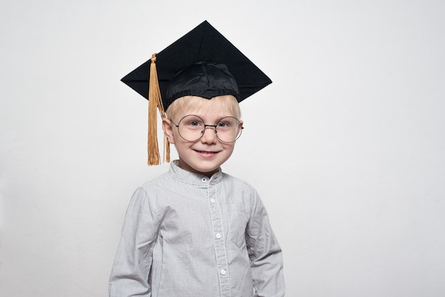 Portrait of a cute blond boy in big glasses and an academic hat.