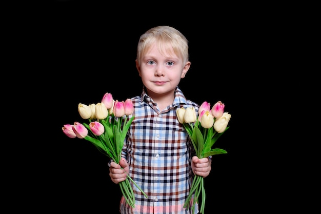 Portrait cute blond boy with a two bouquets of tulips. mother's day concept