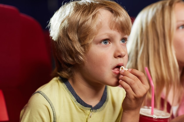 Portrait of cute blonde boy watching movie in cinema theater and eating popcorn, copy space