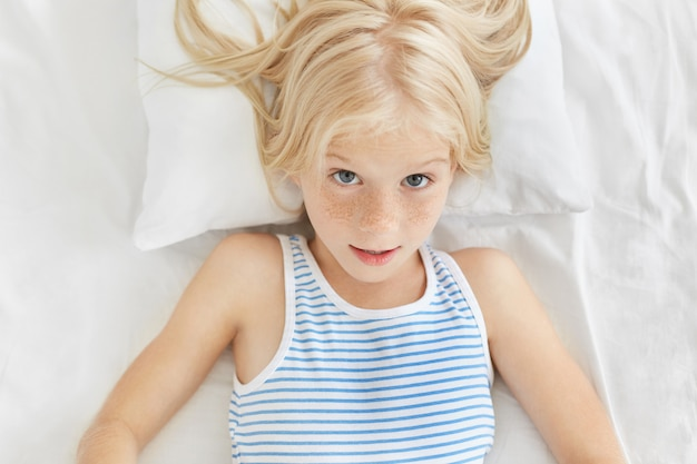Portrait of cute blonde girl wearing sailor t-shirt, looking surprisedly, awaking in morning hearing loud alarm cloak. adorable girl feeling comfort while resting in bed in her room
