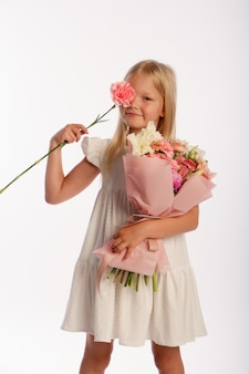 Portrait of cute blonde girl in white dress with beautiful gift bouquet