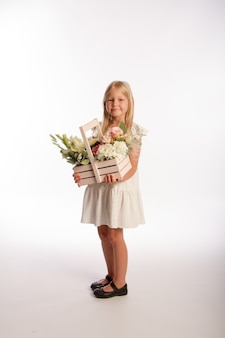 Portrait of cute blonde girl in white dress with wooden basket of flowers