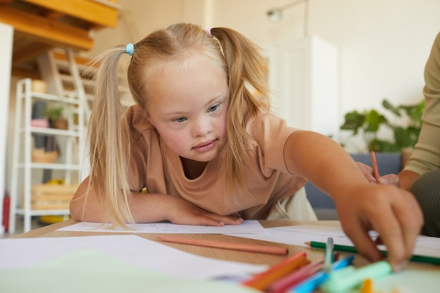 Portrait of cute blonde girl with down syndrome drawing and reaching for pencils while enjoying development class, copy space