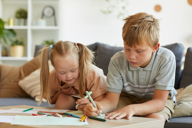 Portrait of cute blonde girl with down syndrome drawing together with older brother at home, copy space