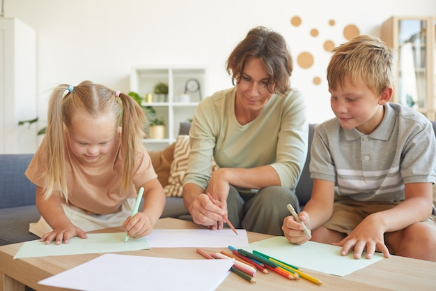 Portrait of cute blonde girl with down syndrome drawing with mother and brother together in home interior