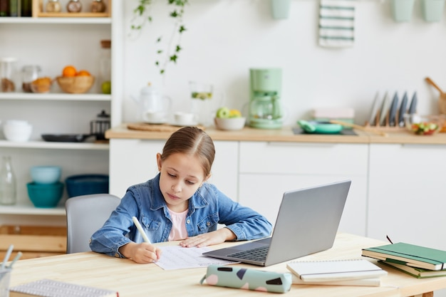 Portrait of cute blonde girl writing in notebook while doing homework or studying online at home in cozy interior, copy space