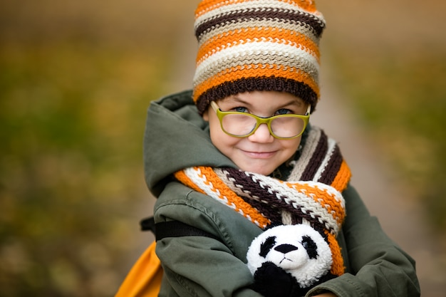 The portrait of cute boy in the glasses and warm knitting hat and scarf with his toy panda in the autumn park