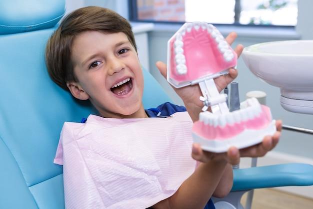 Portrait of cute boy holding dental mold