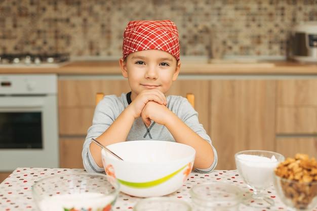 調理しながらカメラを探している肖像画かわいい男の子のシェフ