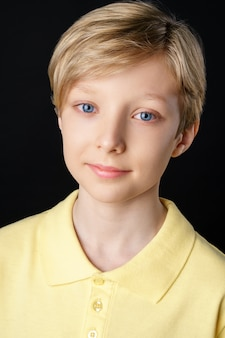 Portrait of a cute boy in a yellow t-shirt on a black background posing for the camera