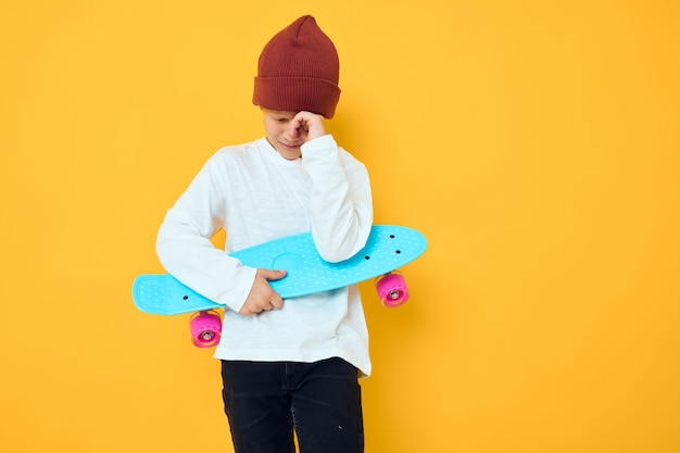 Portrait of cute boys in a white sweater skateboard entertainment childhood lifestyle concept