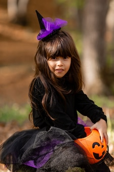 Portrait of a cute brunette girl in a black halloween dress with a basket for sweets