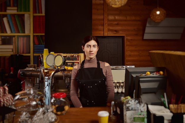 Portrait of a cute brunette woman barista in apron standing behind the bar