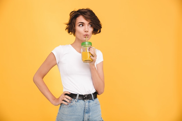 Portrait of a cute casual woman drinking orange juice