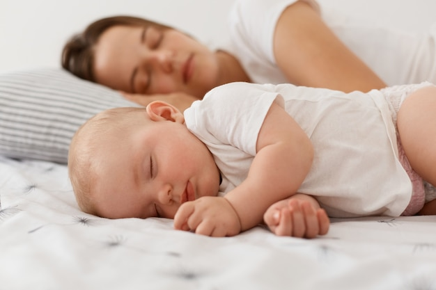 Portrait of cute charming baby girl wearing white clothing lying and sleeping near her lovely mother on bed, having nap, resting at home near mommy with closed eyes.